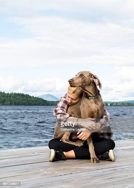 girl hugging dog on dock