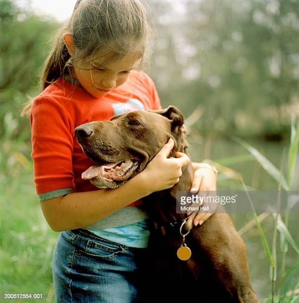 Girl (10-11) hugging dog
