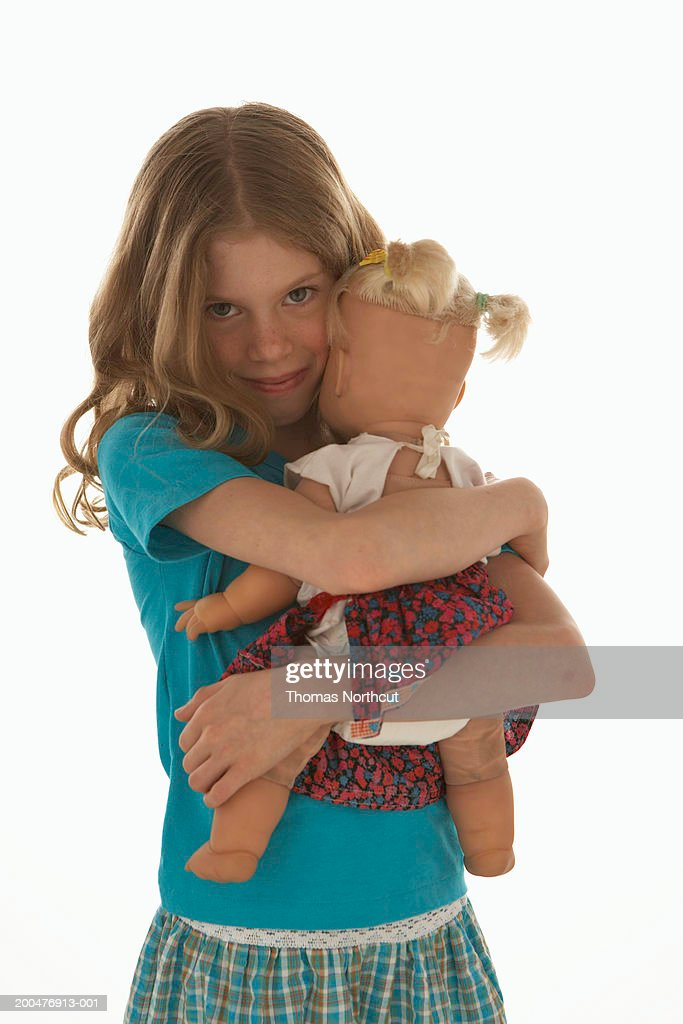 Girl (8-10) hugging doll, smiling, portrait : Stock Photo