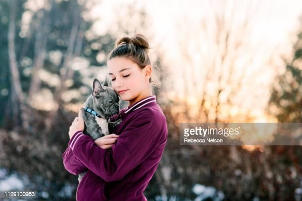 Girl hugging french bulldog puppy outdoors