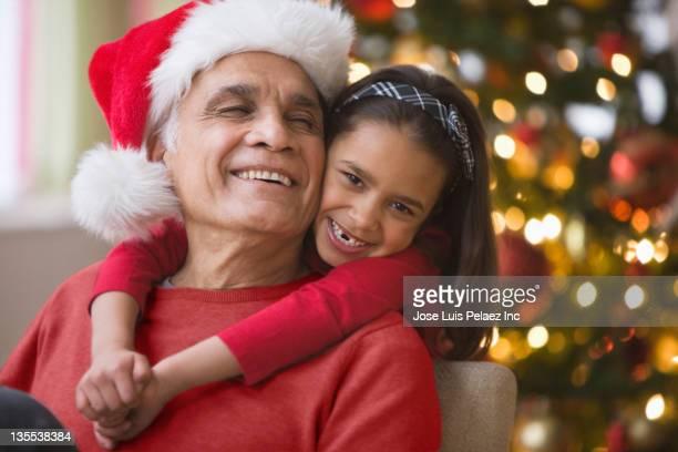 Girl hugging grandfather in Santa hat