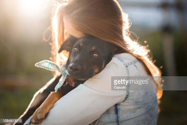 meisje haar hond knuffelen - adoptie stockfoto's en -beelden
