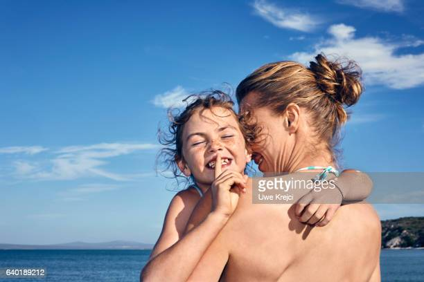 Girl hugging her mother on beach, smiling