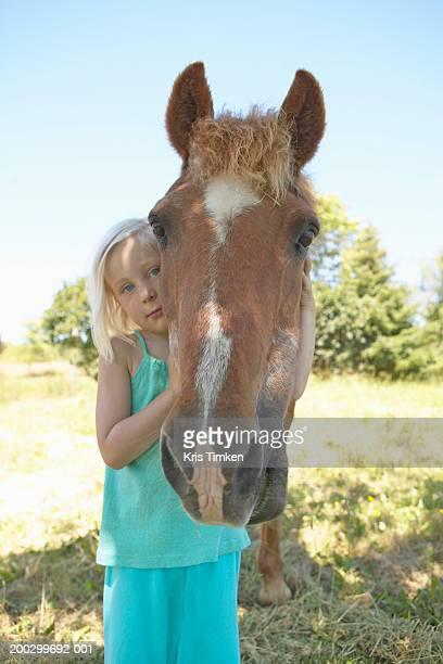Girl (3-5) hugging horse, portrait