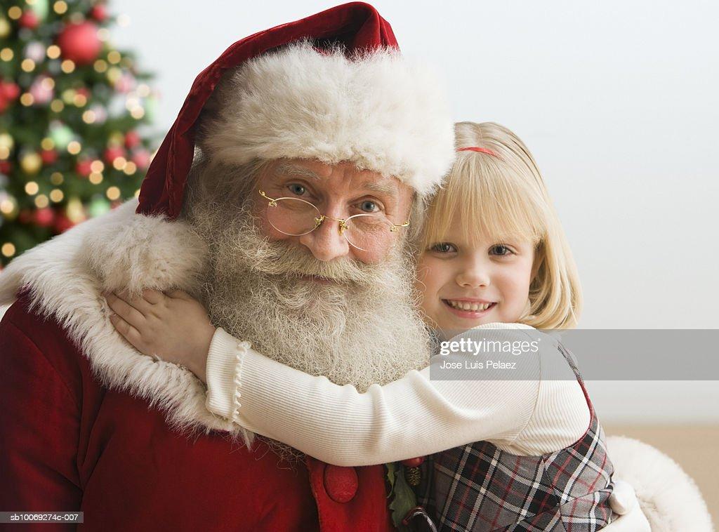 Girl (4-5) hugging Santa Claus, portrait, close-up : Stock Photo