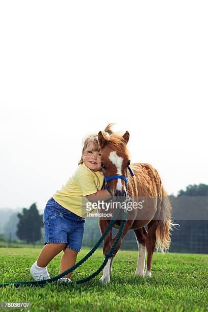 Girl hugging Shetland pony