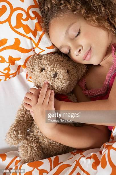 Girl (5-7) hugging teddy bear in bed, eyes closed, elevated view