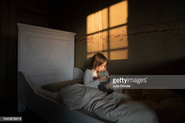 girl hugging teddy bear in bed - angst stockfoto's en -beelden
