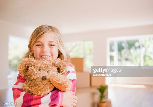 girl hugging teddy bear in new house - teddy bear stock photos and pictures