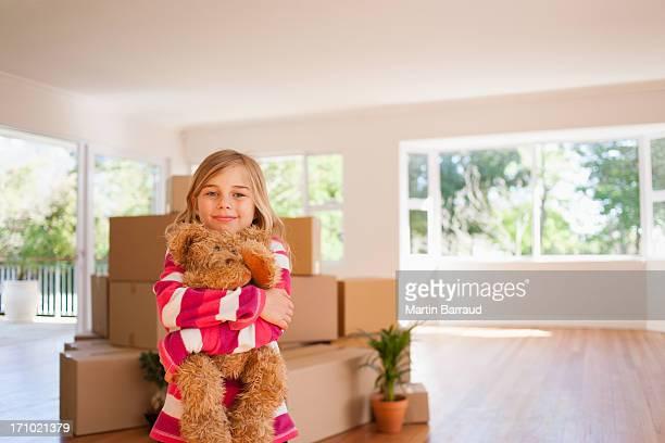 Girl hugging teddy bear in new house