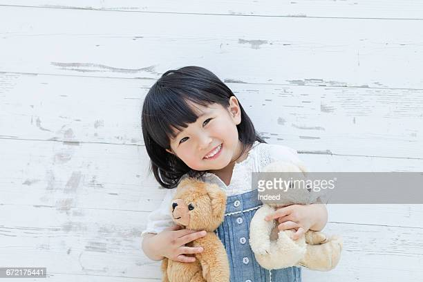 Girl hugging teddy bears