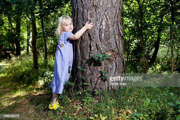 Girl hugging tree in forest
