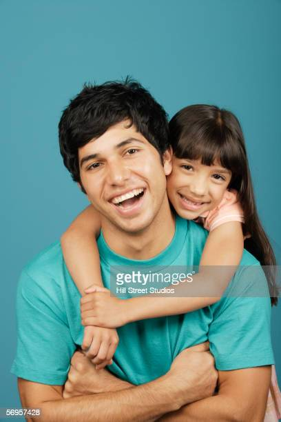 Girl hugging young man around the neck