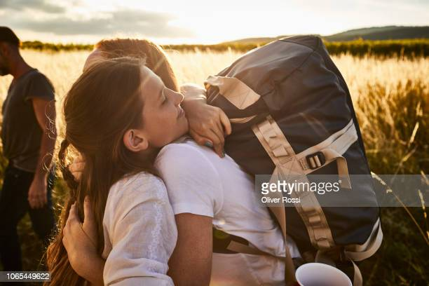 girl hugging young woman with backpack in rural landscape - abschied stock-fotos und bilder