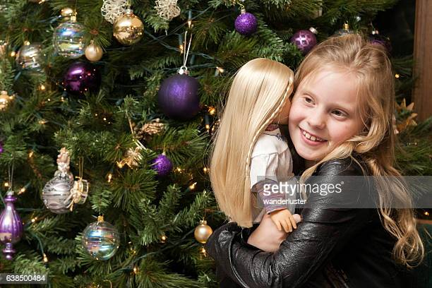 Girl hugs doll at Christmas