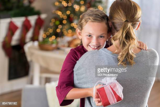 girl hugs mom after receiving christmas gift - little girls giving head stock photos and pictures
