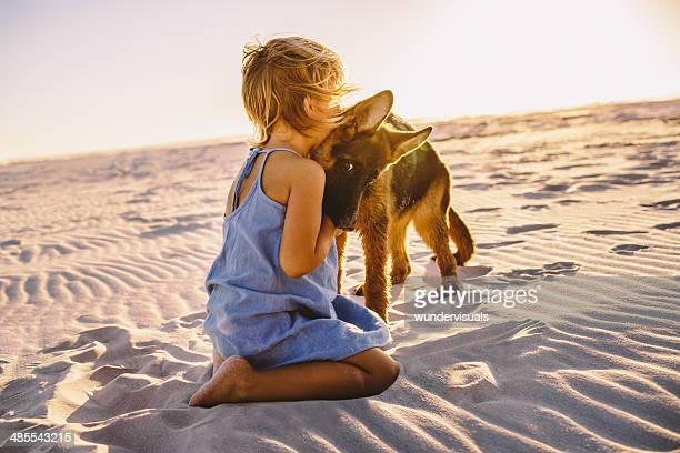 Mädchen umarmt Welpen am Strand