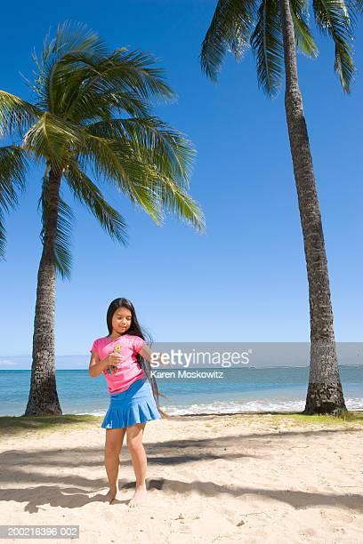 Girl (7-9) hula dancing on beach