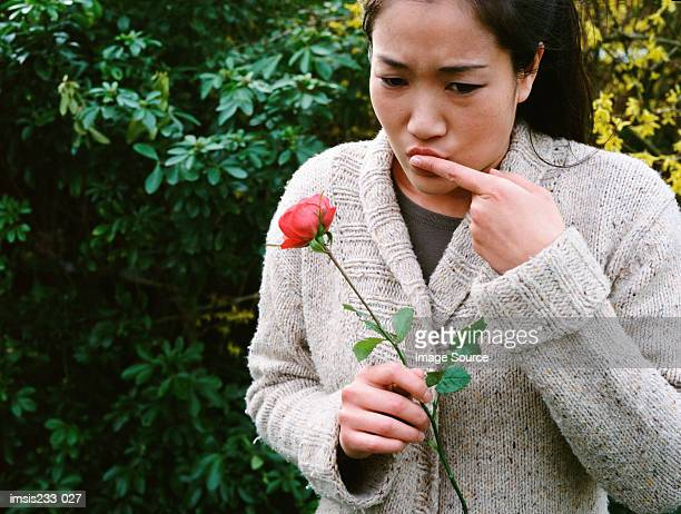 Girl hurts her finger on a rose thorn