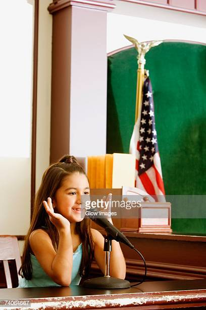 girl imitating a witness sitting in a witness stand - witness stock pictures, royalty-free photos & images