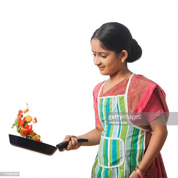 Girl imitating like woman cooking vegetables