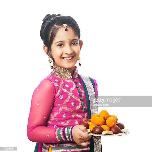 girl imitating like woman holding a plate of assorted sweets on diwali - diwali sweets stock photos and pictures