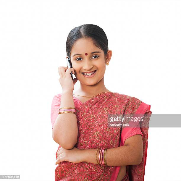 Girl imitating like woman talking on a mobile phone and smiling