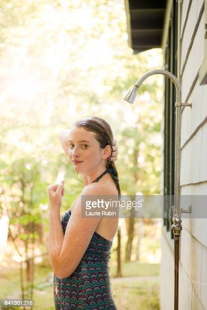 Girl in a bathing suit,outdoor shower in the Summer