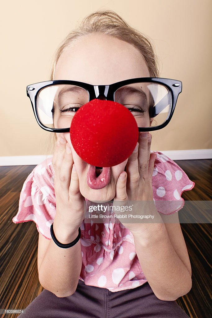 616fbb71a79 A Girl in a Big Red Nose and Geek Glasses   Stock Photo