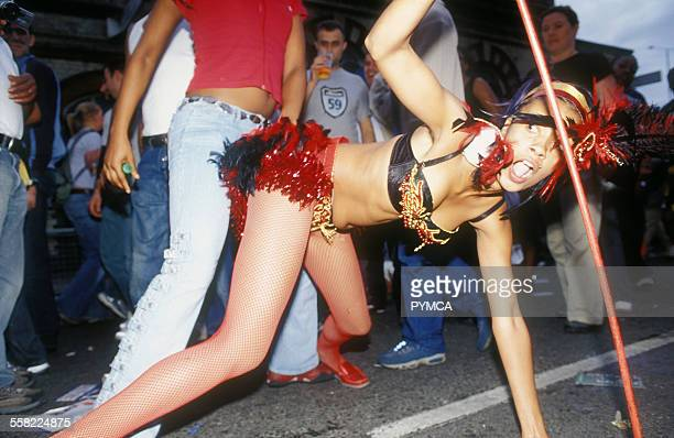 A girl in a carnival costume bending over doing a provocative dance Notting Hill Carnival London UK 2003