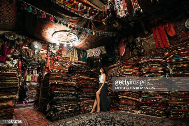 girl in a carpet store - bazaar stockfoto's en -beelden