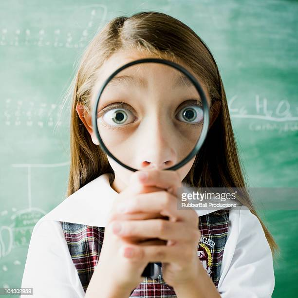 girl in a classroom smiling through a magnifying glass