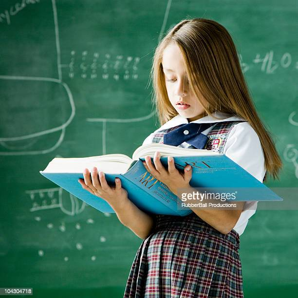 girl in a classroom standing in front of a chalkboard holding a book