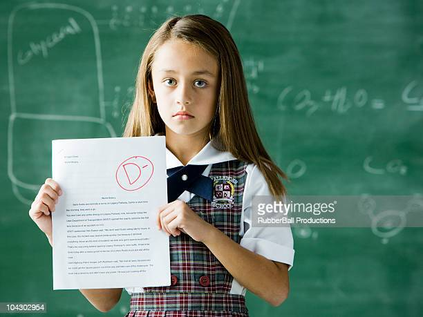 girl in a classroom standing in front of a chalkboard holding a paper with a d minus grade