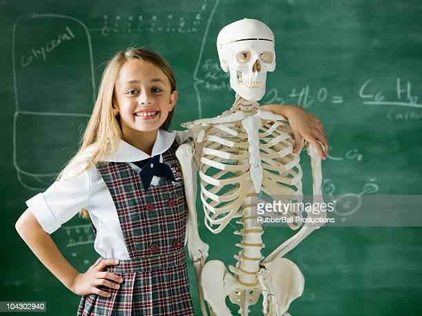 girl in a classroom standing in front of a chalkboard with a human skeleton