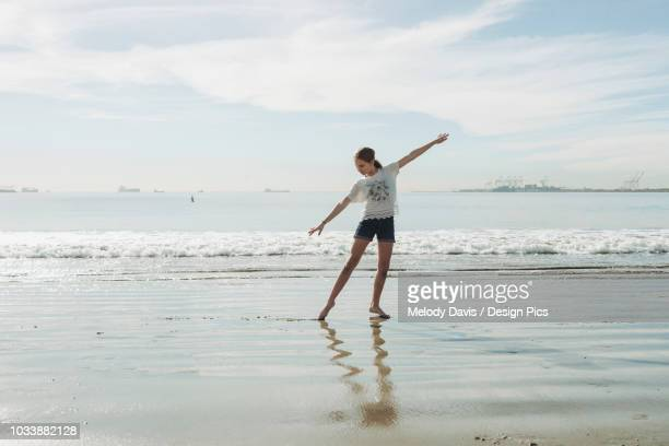 a girl in a dance pose at the beach - wet t shirt girls stock photos and pictures