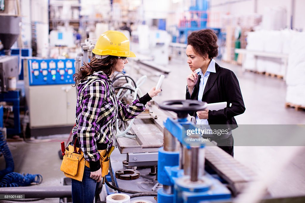 Girl in a factory working with her woman boss : Stockfoto