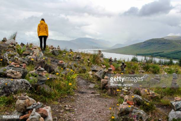 Girl in a field of stone cairns overlooking Loch Loyne, Scotland
