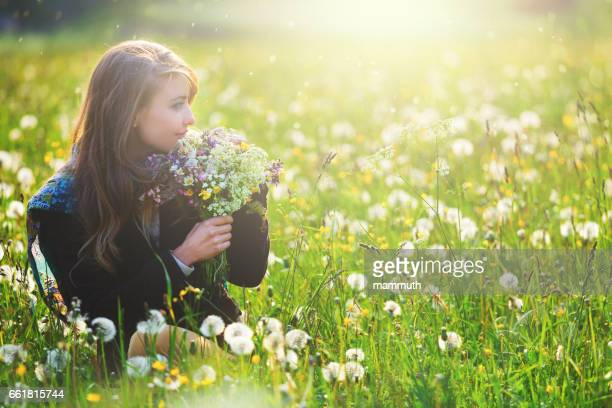 Girl in a flower covered field holding a bouquet