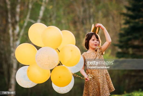 Girl in a gold dress wearing a crown carrying balloons