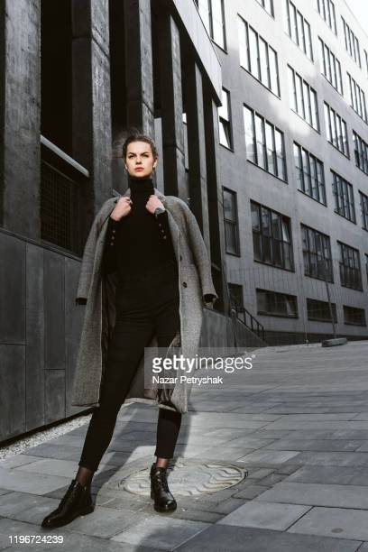 girl in a gray coat  against the backdrop of modern architecture - fashion industry stock pictures, royalty-free photos & images