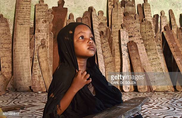 A girl in a madrassa holds a wooden board with verses of the koran written on it in Mogadishu on March 25 2015 AFP PHOTO/Carl de Souza