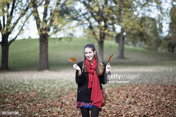 girl in a parc at fall with leaves