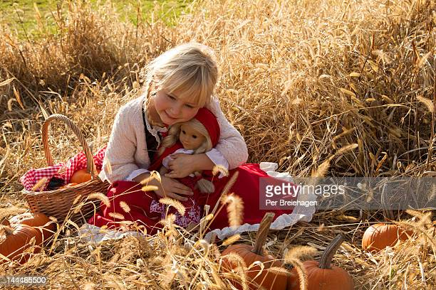 A girl in a pumpkin patch with her doll