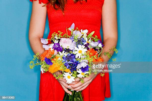 Girl in a red dress holding flowers.