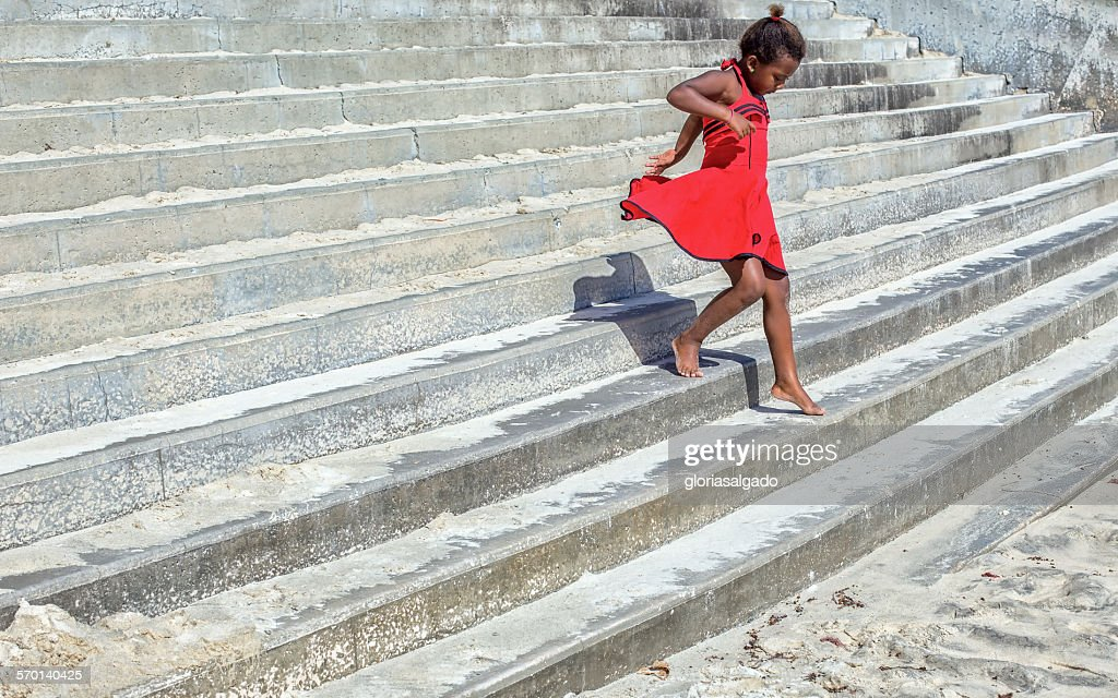 Girl in a red dress running down steps : Stock Photo