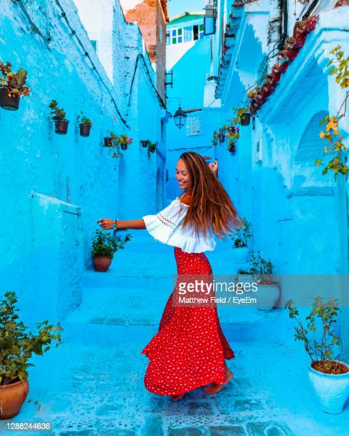 girl in a red skirt dancing in the middle of the street in the blue city of chefchaouen in morocco - femme marocaine photos et images de collection