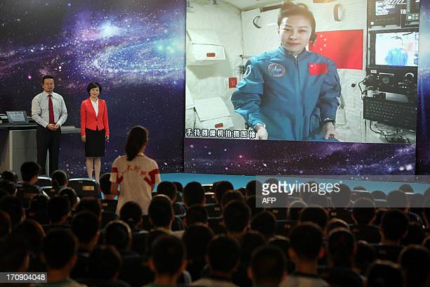 A girl in a school in Beijing asks Chinese female astrounaut Wang Yaping questions as Wang delivers a lesson to students from Tiangong1 space module...