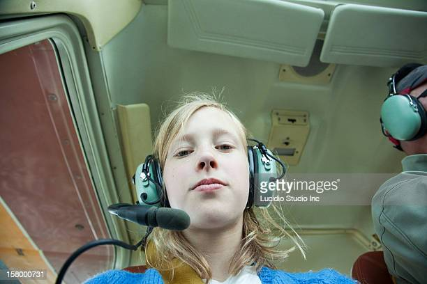 Girl in a small airplane, wearing headphones