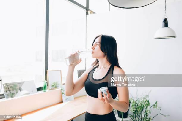 a girl in a sports uniform drinks water near the window. - sports uniform ストックフォトと画像